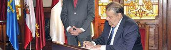 De pie, Pedro Sanjurjo González, presidente de la Junta General del Principado de Asturias  y, firmando en el Libro de Honor, Jesús Fernández Vaquero, presidente de las Cortes de CLM.