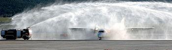 """En la imagen, los bomberos del aeropuerto de Ciudad Real hacen el """"bautizo de agua"""" al avión TRJ 55 de Air Nostrum procedente de Barcelona que fue el primer avión comercial que aterrizó en el aeródromo manchego el pasado 19 de diciembre."""