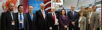 El rector de la UCLM, Ernesto Martínez Ataz, junto al rector honorario, miembros de su equipo y personal de la institución, en el stand de la UCLM en España Original.