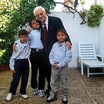 El Padre Ángel abraza a niños iraquíes en el jardín de la casa de Olías.