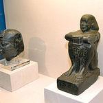 A la i. de la foto, Cabeza Real. Alejandría. Ptolomeo II o III (285-221 a.C.). Granito negro; a la d. de la foto, Estatua de Harsomtusemhat ¿Menfis? Reinado Psamético I (664-610 a.C.). Basalto.