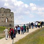 Imagen de unos visitantes al Parque Arqueológico de Carranque junto al muro del Edificio Palatium.